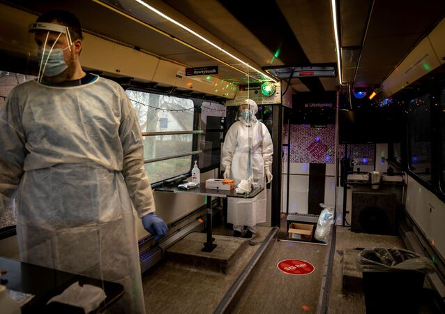 Healthcare workers wait in the Partybus, where people can listen to music while being tested for the coronavirus disease (COVID-19), in Ishoej, Denmark February 23, 2021