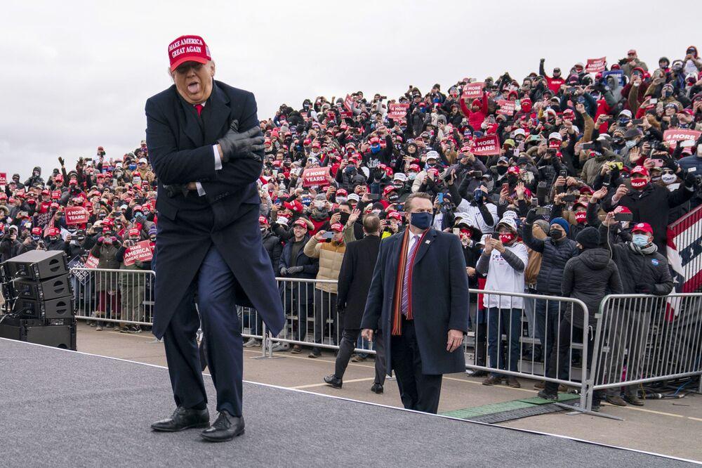 L'ex presidente Donald Trump scherza sul tempo freddo mentre arriva per un comizio elettorale al Michigan Sports Stars Park, domenica 1 novembre 2020, a Washington, USA