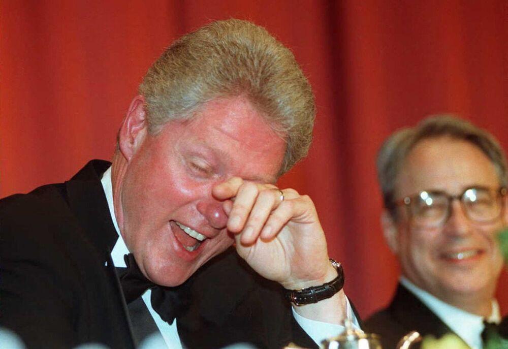 L'ex presidente degli Stati Uniti Bill Clinton asciuga le lacrime di risate mentre lui e il Presidente dell'Associazione dei Corrispondenti della Casa Bianca Carl P. Leubsdorf ascoltano la battuta del comico Al Franken durante la cena annuale dell'associazione a Washington, il 4 maggio 1996