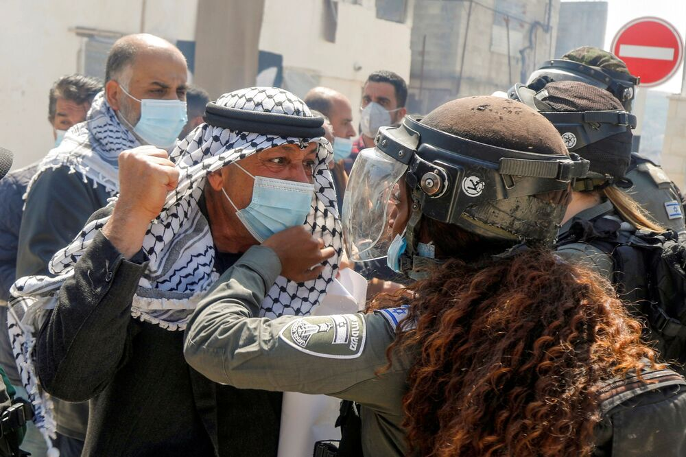 Un manifestante palestinese litiga con una poliziotta di frontiera israeliana durante una manifestazione in occasione della Giornata della terra, a Sebastia vicino a Nablus, Cisgiordania, il 30 marzo 2021