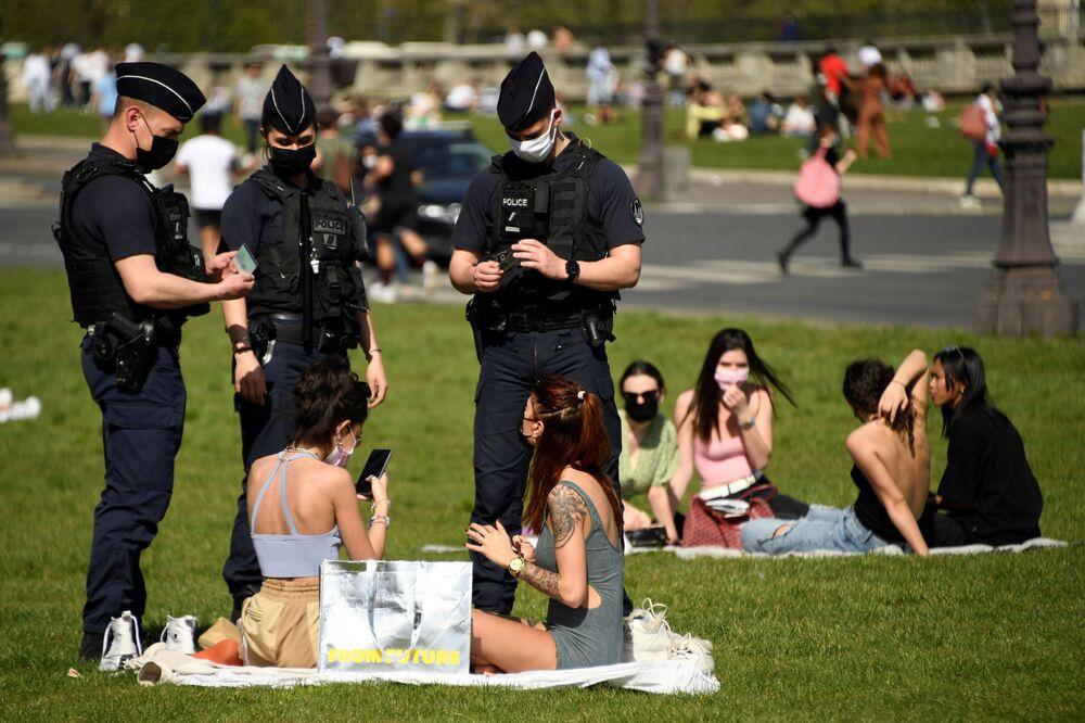 Gli agenti di polizia controllano le persone che si godono una soleggiata giornata primaverile sull'erba di fronte all'Hotel des Invalides a Parigi, il 31 marzo 2021