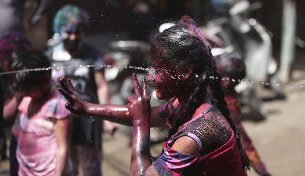 I bambini indiani spruzzano acqua mentre celebrano Holi a Jammu, in India, domenica 28 marzo 2021