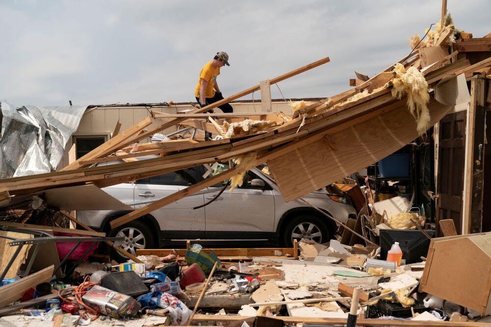 Nathan Mason valuta i danni alla casa di sua nonna il giorno dopo che una serie di tornado ha colpito città di Ohatchee, USA, il 26 marzo 2021