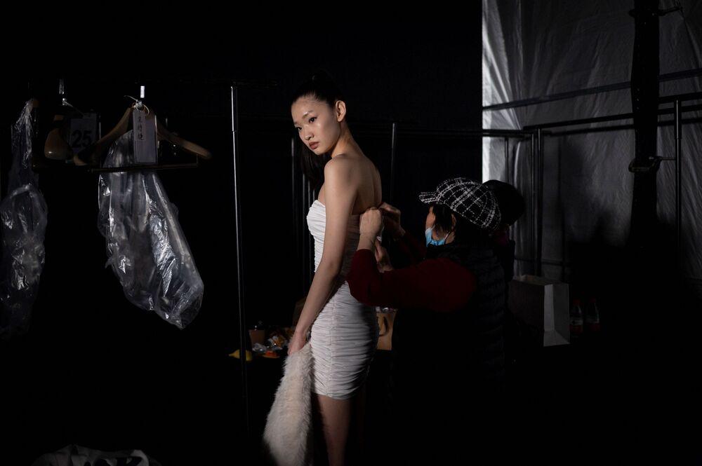 Una modella si prepara per la sfilata durante la China Fashion Week a Pechino, il 28 marzo 2021