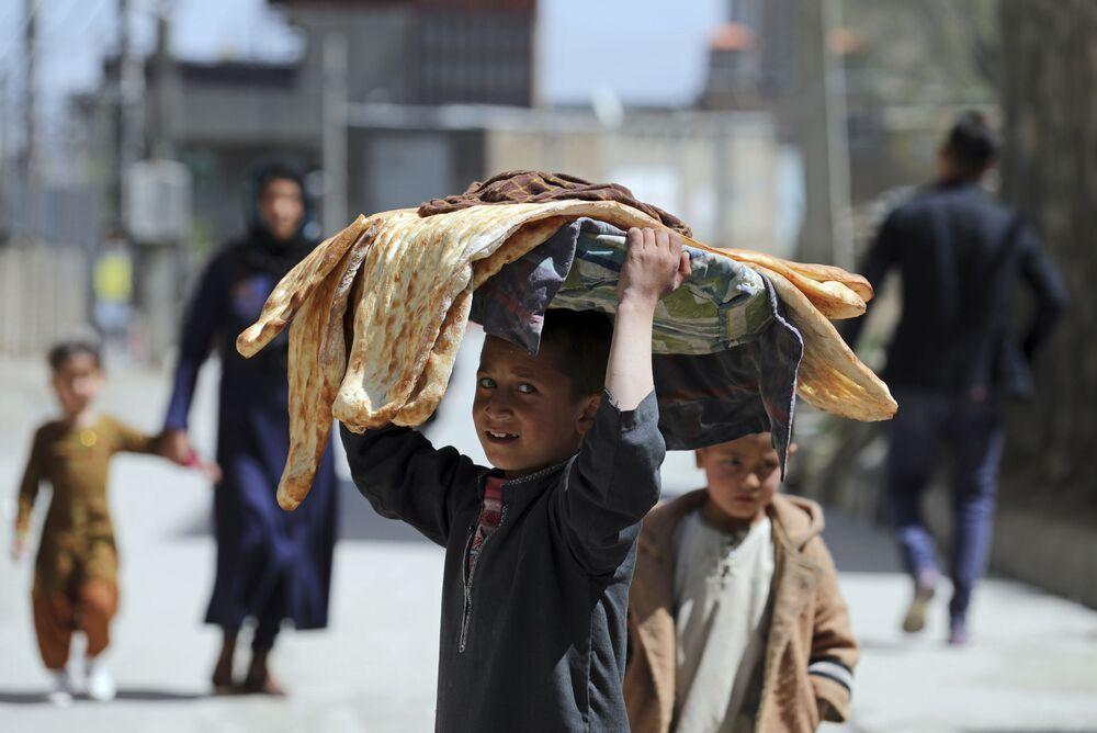 Un ragazzo afghano porta il pane sulla testa a Kabul, Afghanistan, lunedì 29 marzo 2021