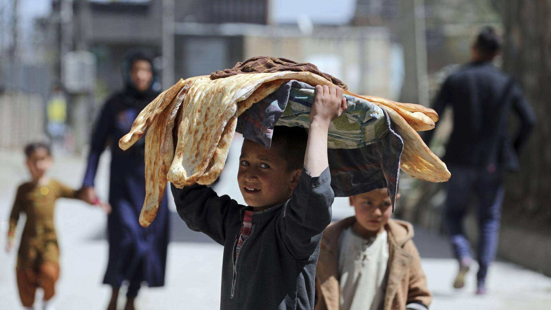 Мальчик с хлебом на голове на одной из улиц Кабула, Афганистан - Sputnik Italia, 1920, 13.08.2021