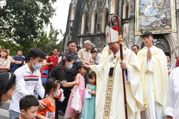 Il vescovo Joseph Vu Van Thien saluta i fedeli cattolici dopo una messa di Pasqua nella cattedrale di San Giuseppe ad Hanoi, Vietnam, il 4 aprile 2021 - Sputnik Italia