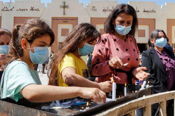 Le persone accendono le candele dopo una messa pasquale, fuori dalla chiesa caldea di Sant'Elia a Baghdad, in Iraq, il 4 aprile 2021 - Sputnik Italia
