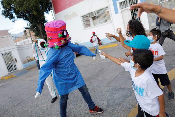 I bambini spruzzano alcool e antisettico su una persona che indossa un costume da coronavirus in Venezuela - Sputnik Italia
