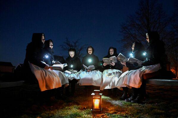 Donne vestite con abiti tradizionali della comunità etnica slava dei Sorbi di Lusazia si sono riunite per Pasqua per cantare davanti a una chiesa a Schleife, Germania, il 4 aprile 2021 - Sputnik Italia