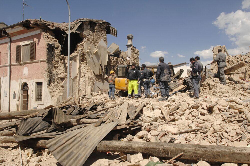 I soccorritori e i volontari rimuovono i detriti dopo un forte terremoto in Abruzzo, Italia, lunedì 6 aprile 2009