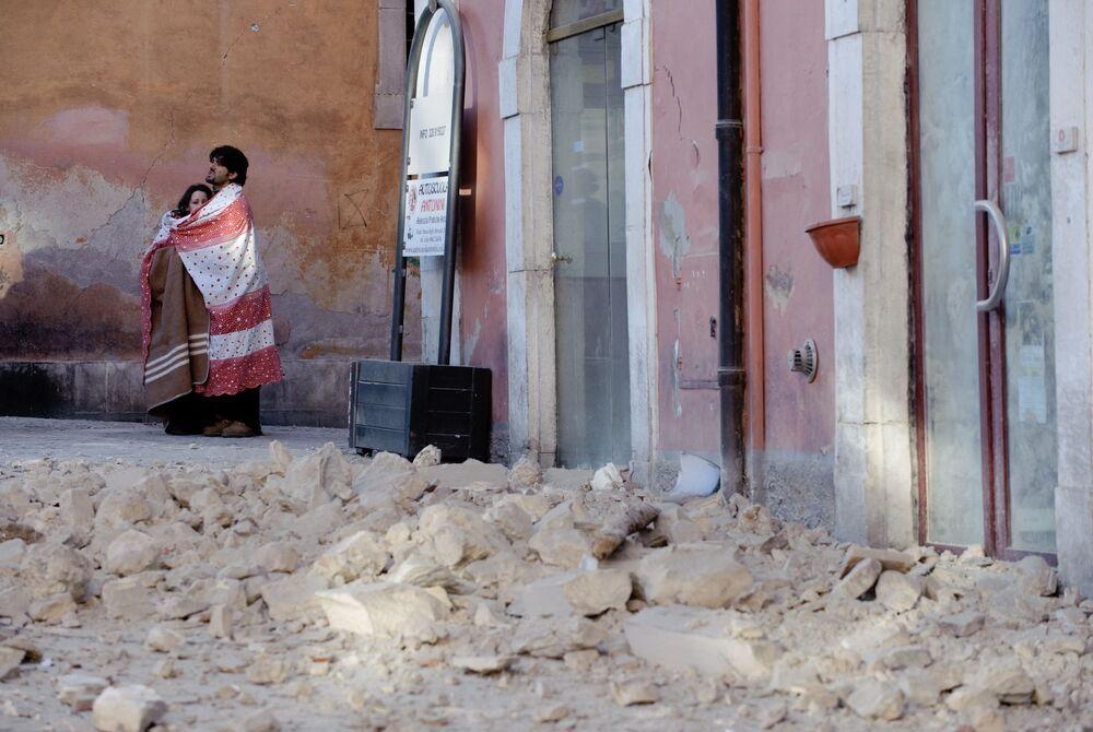 Una coppia tra le macerie dopo il terremoto dell'Aquila, il 6 aprile 2009
