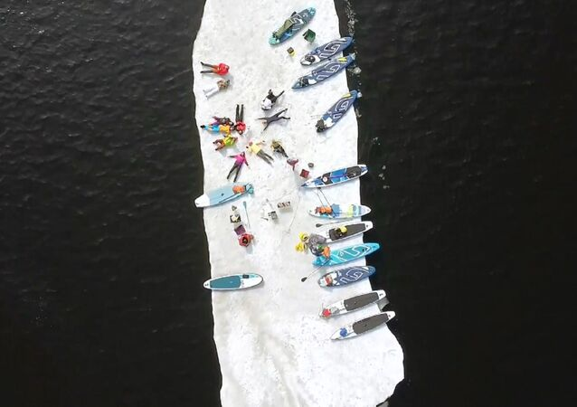 In Russia appassionati di sup surf fanno un giro su...una lastra di ghiaccio