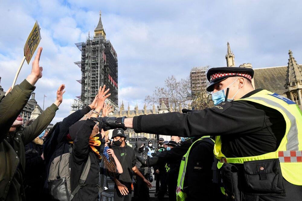 I dimostranti alzano le mani mentre affrontano i poliziotti durante una protesta a Londra