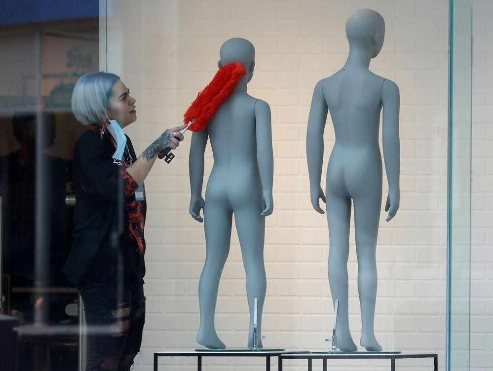 Una ragazza spolvera i manichini di un negozio di abbigliamento prima della riapertura a Liverpool, Regno Unito