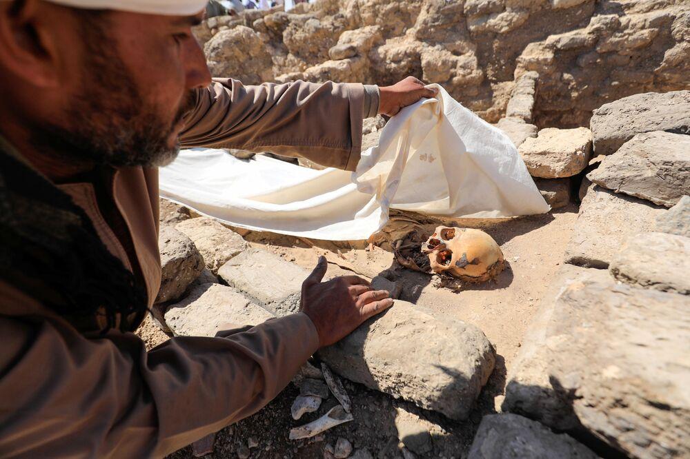Un uomo guarda i resti umani scheletrici nella Città d'oro perduta'', che è stata recentemente scoperta dagli archeologi, nei pressi di Luxor, nell'Alto Egitto, il 10 aprile 2021