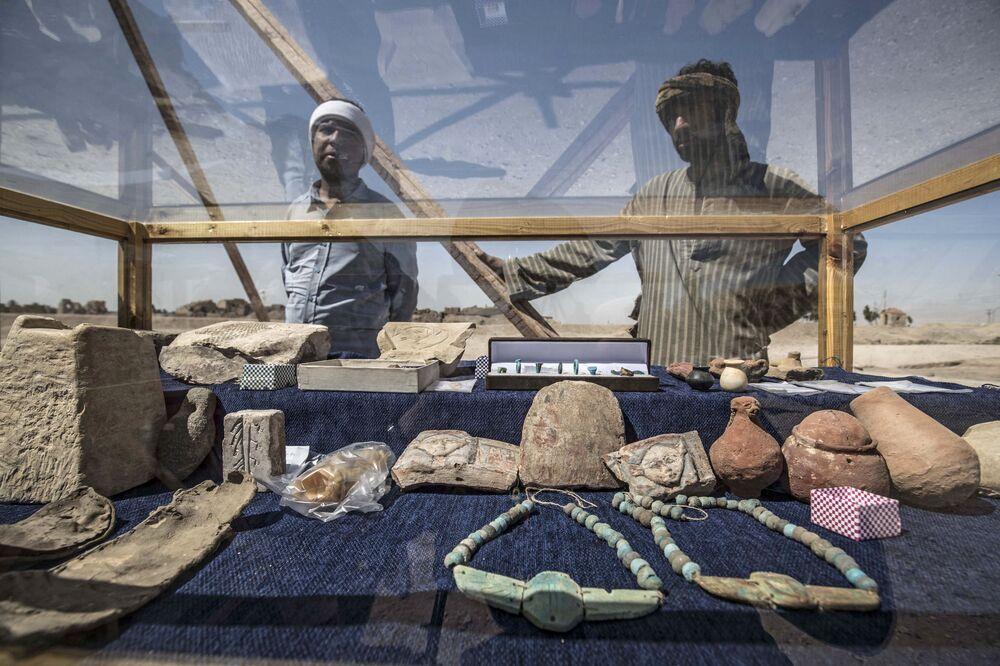 I lavoratori guardano un'esposizione di manufatti scoperti