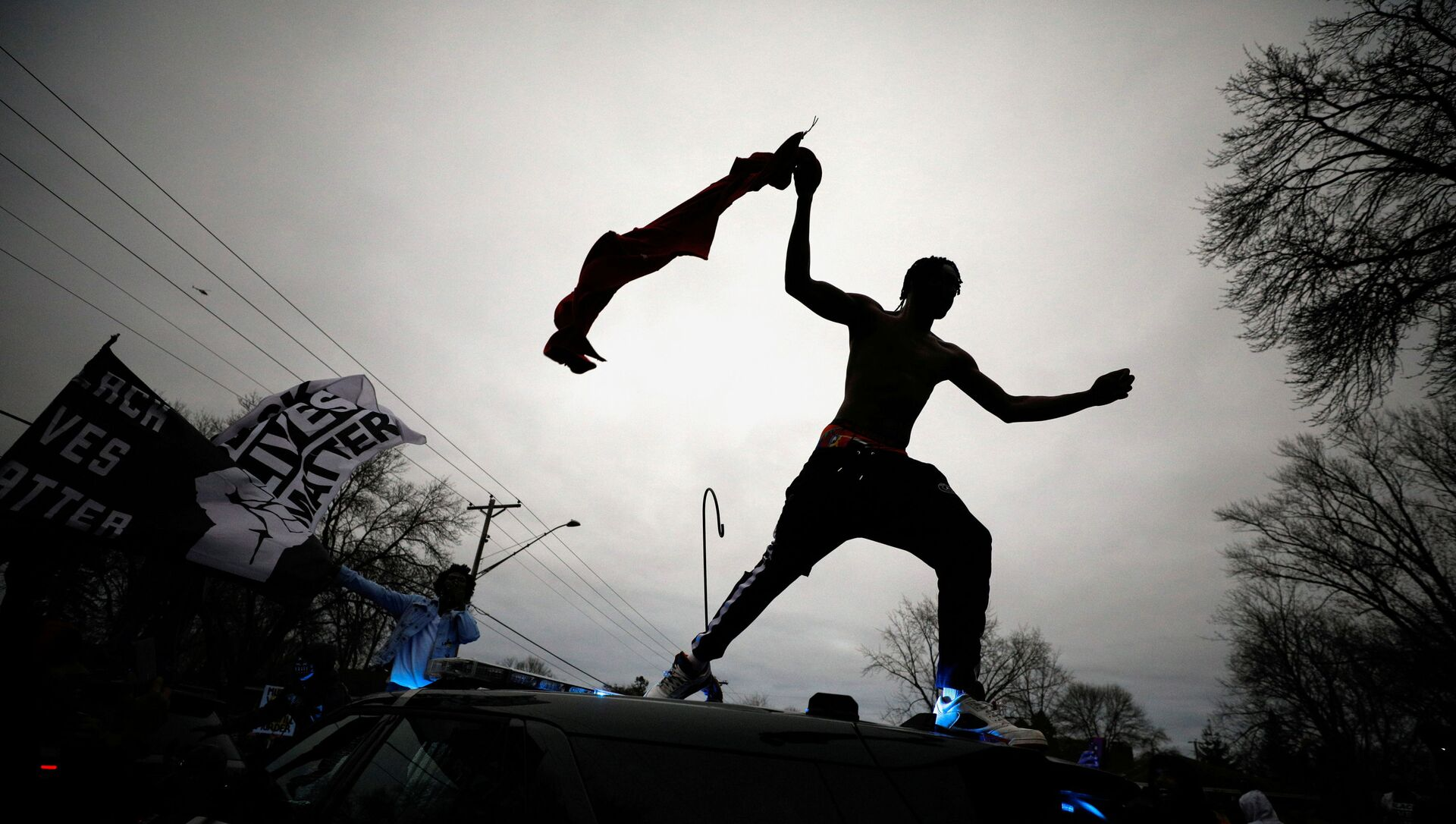 A demonstrator jumps off a police cruiser during a protest after police allegedly shot and killed a man, who local media report is identified by the victim's mother as Daunte Wright, in Brooklyn Center, Minnesota, U.S., April 11, 2021. - Sputnik Italia, 1920, 12.04.2021