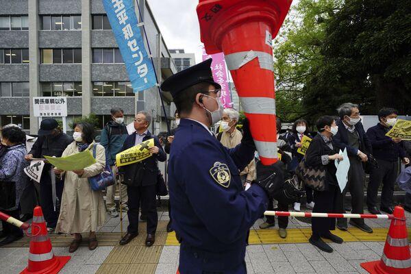 Le persone protestano contro la decisione del governo di rilasciare enormi quantità di acqua radioattiva dalla centrale nucleare di Fukushima nell'oceano, davanti alla residenza del Primo ministro giapponese a Tokyo martedì 13 aprile 2021 - Sputnik Italia