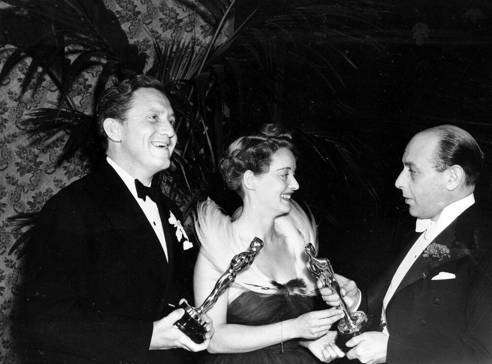 L'attore britannico Sir Cedric Hardwicke consegna gli Oscar a Bette Davis e Spencer Tracy il 23 febbraio 1939