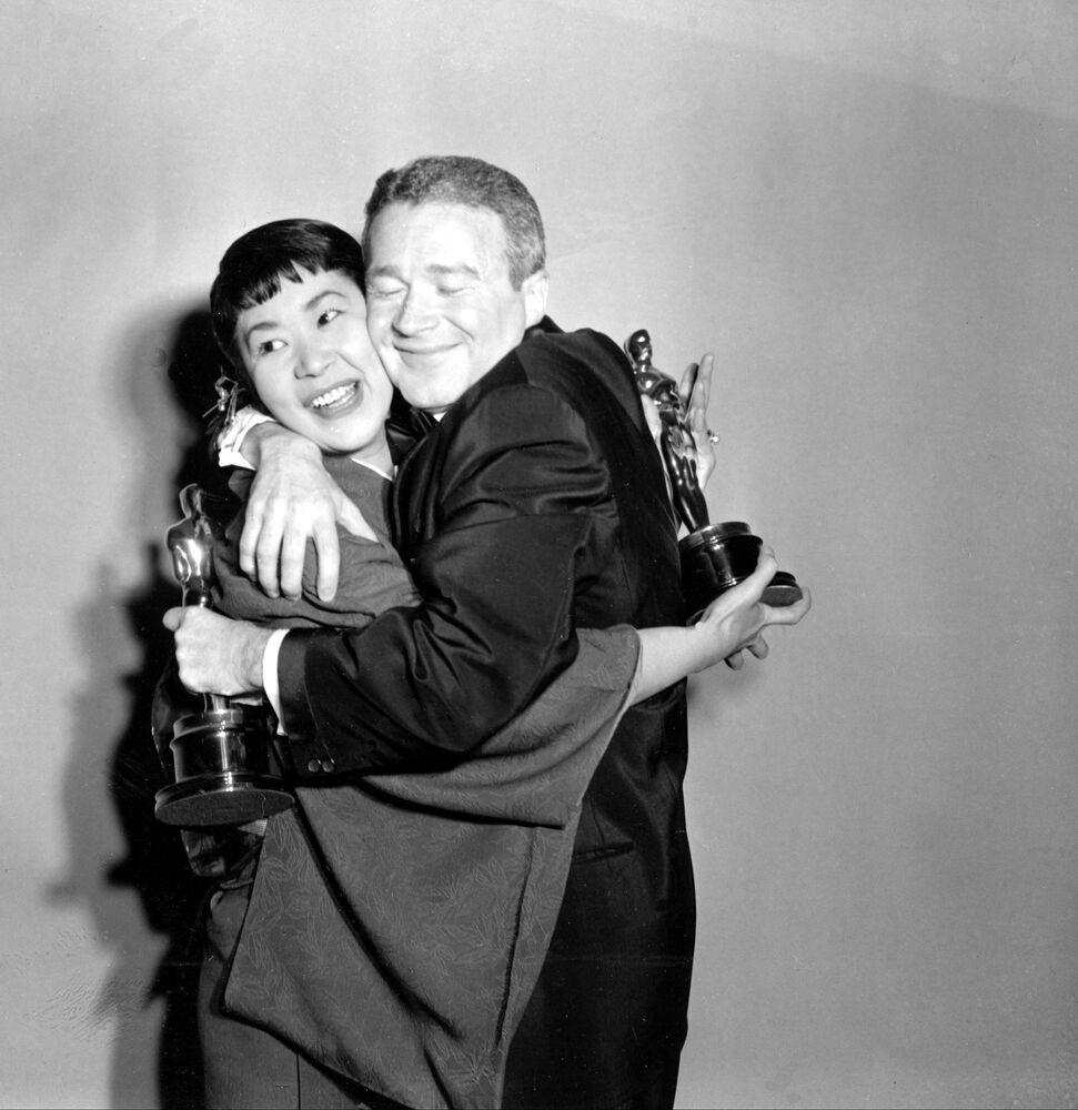 Miyoshi Umeki e Red Buttons si abbracciano durante la Cerimonia di premiazione annuale degli Oscar, il 26 marzo 1958