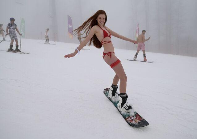 Una partecipante al carnevale BoogelWoogel-2021 durante una discesa di massa dalla montagna in costume da bagno presso la stazione sciistica di Rosa Khutor a Sochi, Russia