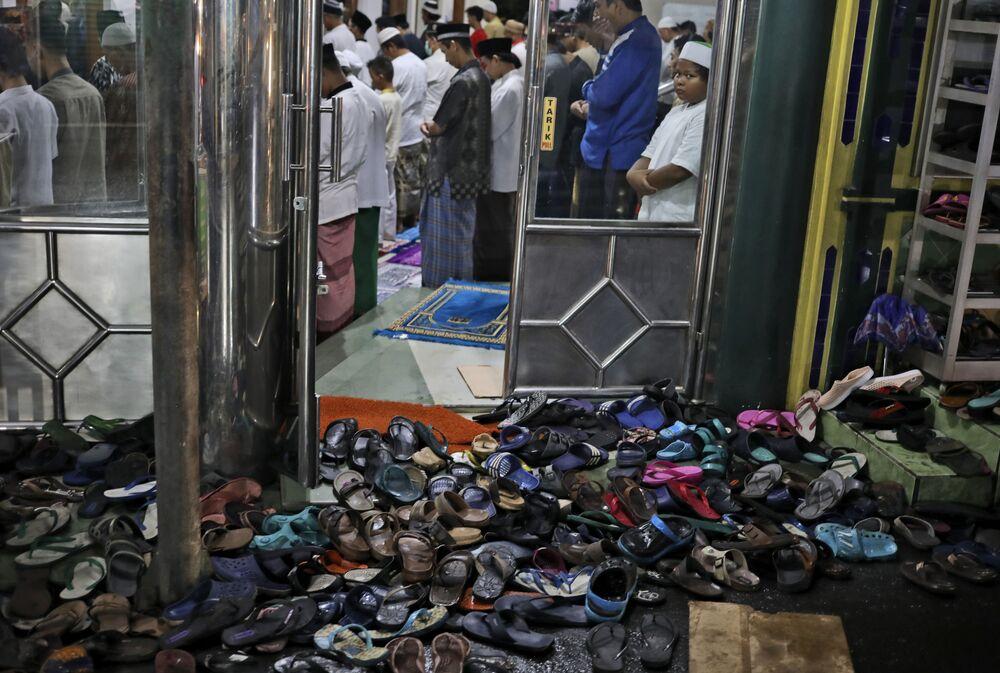 Le calzature vengono lasciate fuori mentre le persone eseguono una preghiera serale del Tarawih durante la prima sera del sacro mese di digiuno del Ramadan, in una moschea a Giacarta, Indonesia, lunedì 12 aprile 2021
