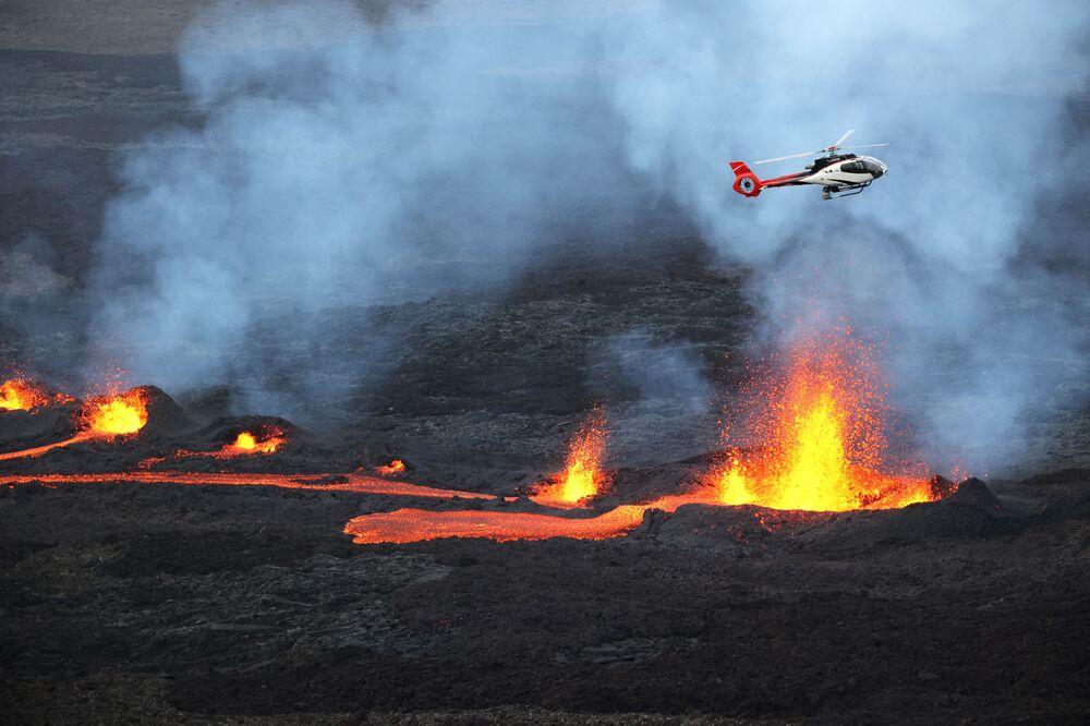 Un elicottero che vola mentre la lava sta eruttando dal vulcano Piton de la Fournaise sull'isola La Riunione, un dipartimento francese nell'Oceano Indiano
