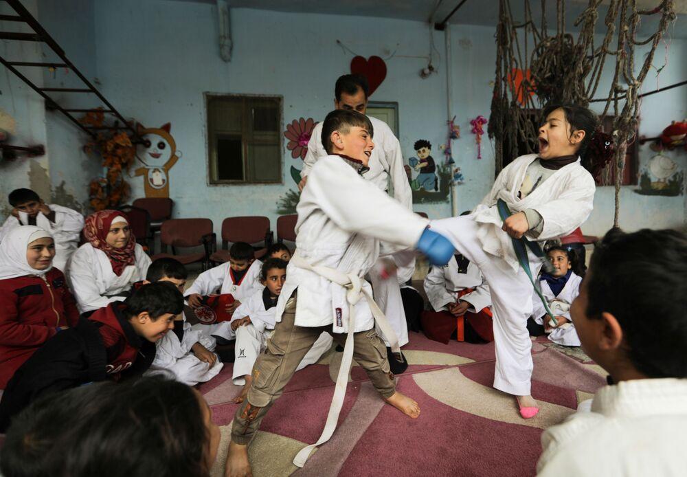 I bambini praticano arti marziali durante un allenamento in una scuola nel villaggio siriano di al-Jeineh, in Siria, l'11 aprile 2021
