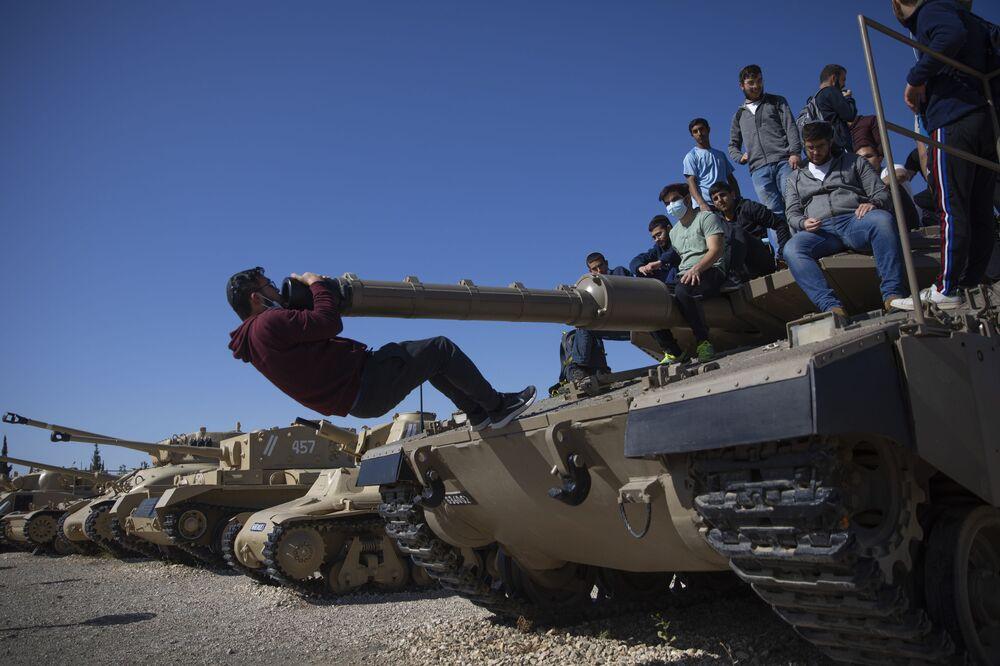Gli studenti salgono su un carro armato durante una cerimonia che segna l'annuale Giorno della memoria per ricordare i soldati caduti e le vittime del terrore, presso il sito commemorativo del Corpo corazzato israeliano a Latrun, Israele, mercoledì 14 aprile 2021