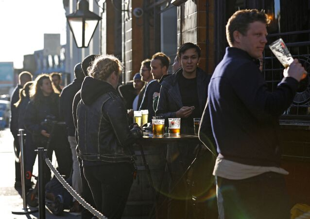 After-work drinkers enjoy a pint outside a pub in Borough Market, in London on September 25, 2020, as new earlier closing times for pubs and bars in England and Wales are introduced to combat the spread of the coronavirus.