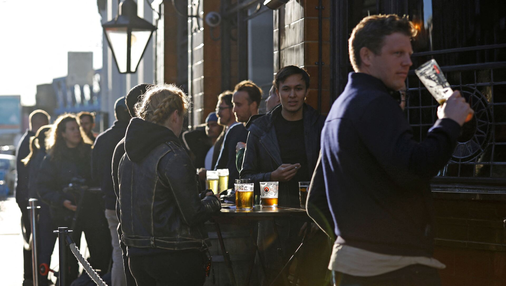 After-work drinkers enjoy a pint outside a pub in Borough Market, in London on September 25, 2020, as new earlier closing times for pubs and bars in England and Wales are introduced to combat the spread of the coronavirus. - Sputnik Italia, 1920, 22.04.2021