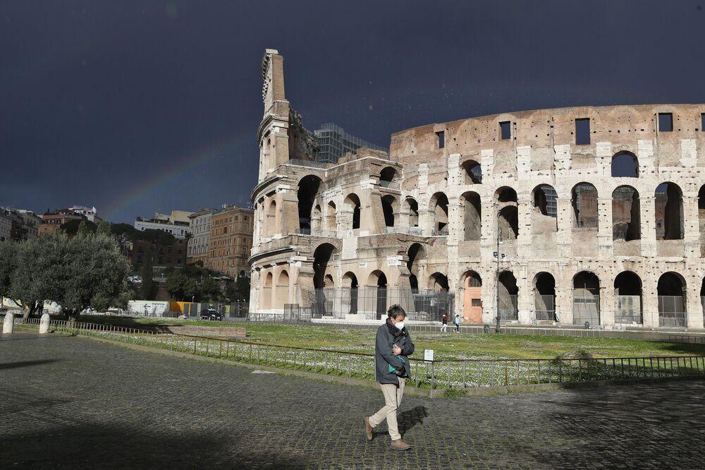Un uomo che indossa una mascherina protettiva vicino al Colosseo a Roma