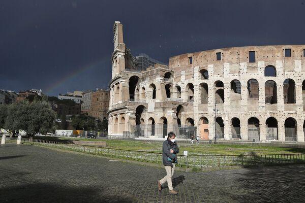 Un uomo che indossa una mascherina protettiva vicino al Colosseo a Roma - Sputnik Italia