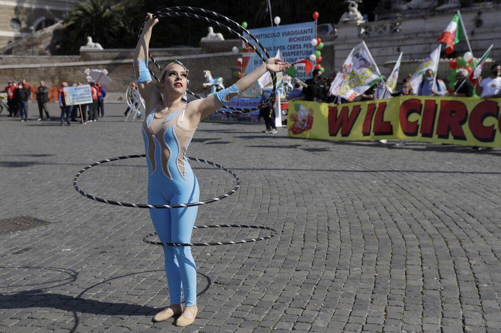 Un artista circense si esibisce davanti a uno striscione con la scritta Viva il circo durante una manifestazione di artisti circensi a Roma