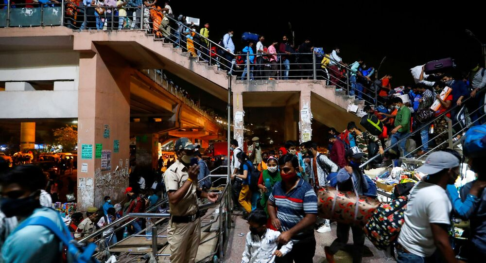 I lavoratori migranti arrivano in una stazione degli autobus per tornare nei loro villaggi dopo che il governo di Delhi ha ordinato un blocco di sei giorni per limitare la diffusione della malattia da coronavirus (COVID-19), a Ghaziabad, alla periferia di Nuova Delhi, in India, 19 aprile 2021.