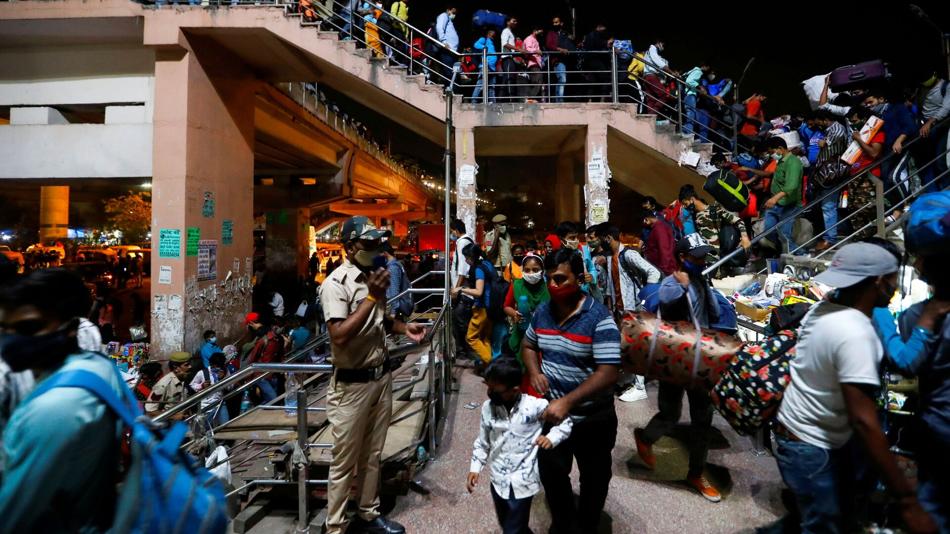 I lavoratori migranti arrivano in una stazione degli autobus per tornare nei loro villaggi dopo che il governo di Delhi ha ordinato un blocco di sei giorni per limitare la diffusione della malattia da coronavirus (COVID-19), a Ghaziabad, alla periferia di Nuova Delhi, in India, 19 aprile 2021. - Sputnik Italia, 1920, 22.04.2021