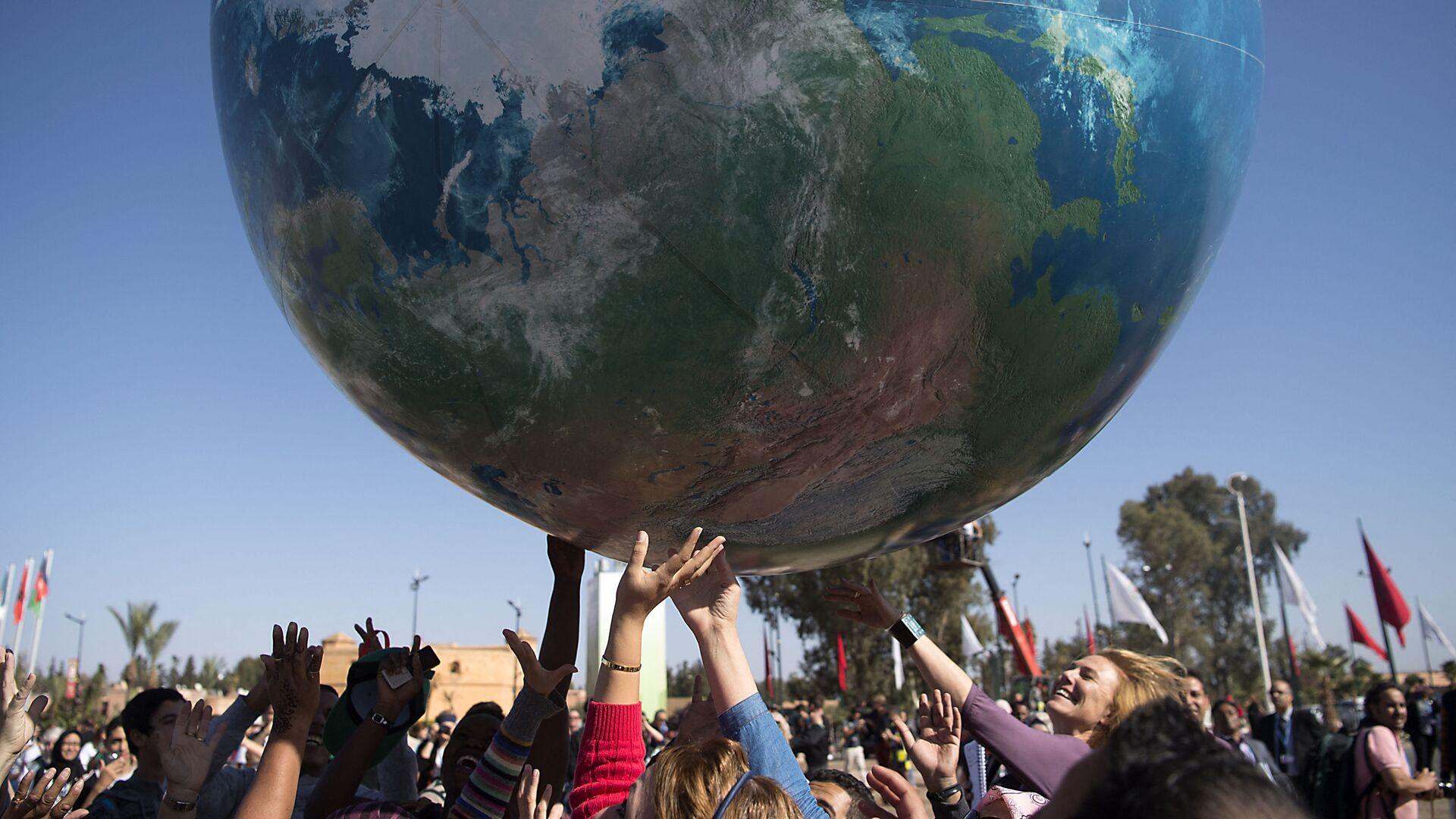 Члены всемирной конференции ООН по вопросам изменения климата с макетом Земли - Sputnik Italia, 1920, 06.06.2021