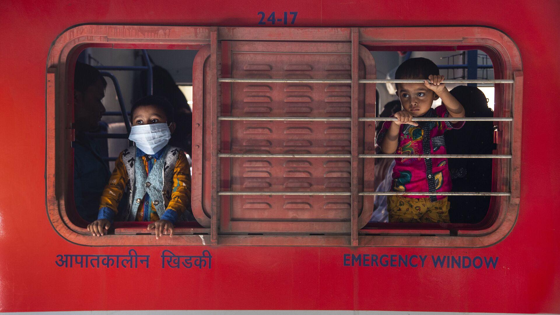 Мальчики смотрят в окно поезда на железнодорожной станции в Гаухати, Индия - Sputnik Italia, 1920, 05.06.2021