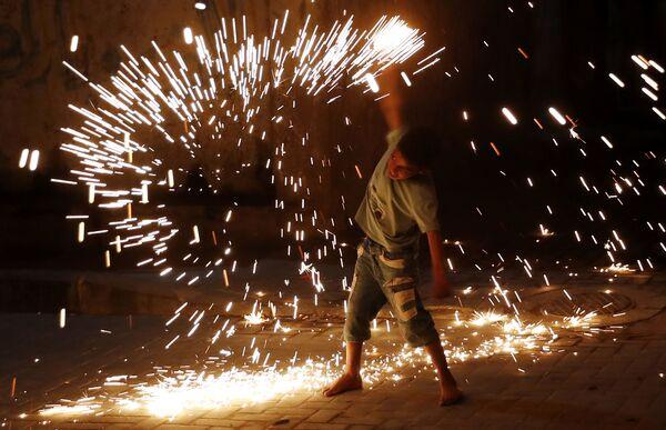 Un ragazzo gioca con i fuochi d'artificio durante le celebrazioni del Ramadan a Gaza City, 20 aprile 2021.  - Sputnik Italia