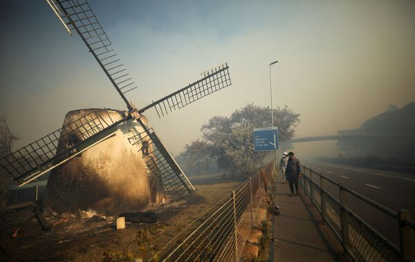 Lo storico Mostert Mill brucia mentre i vigili del fuoco combattono per estinguere un incendio a Cape Town, Sud Africa.  - Sputnik Italia