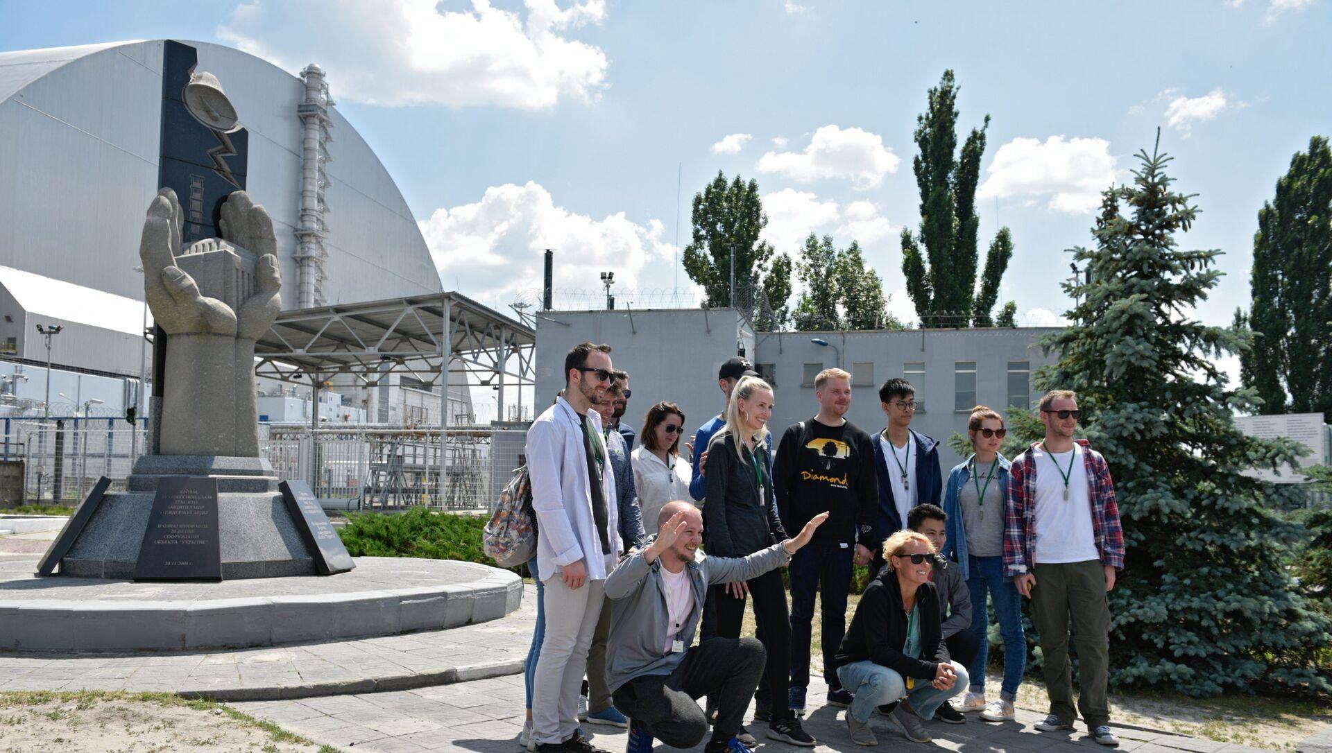 Chernobyl, oggi: turisti davanti al monumento ai liquidatori, sullo sfondo del nuovo sarcofago che ricopre il reattore 4 - Sputnik Italia, 1920, 18.05.2021