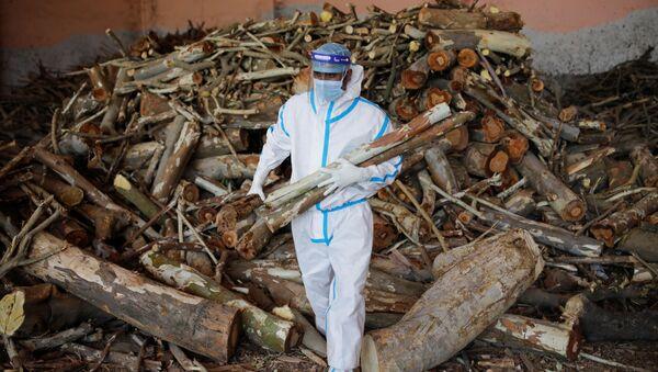 Мужчина несет дрова для подготовки погребальных костров во время массовой кремации в крематории в Нью-Дели, Индия - Sputnik Italia