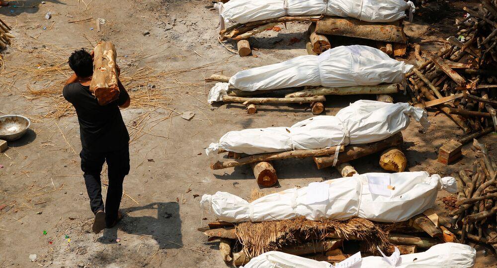 Un uomo con legna da ardere passa davanti alle pire funerarie durante la cremazione di massa in India
