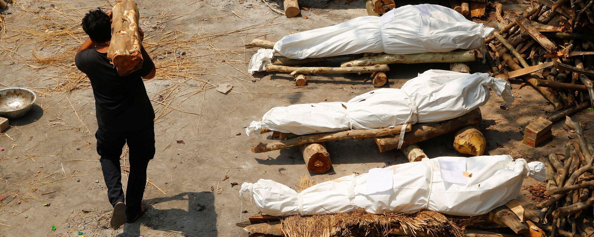 Un uomo con legna da ardere passa davanti alle pire funerarie durante la cremazione di massa in India - Sputnik Italia, 1920, 28.04.2021