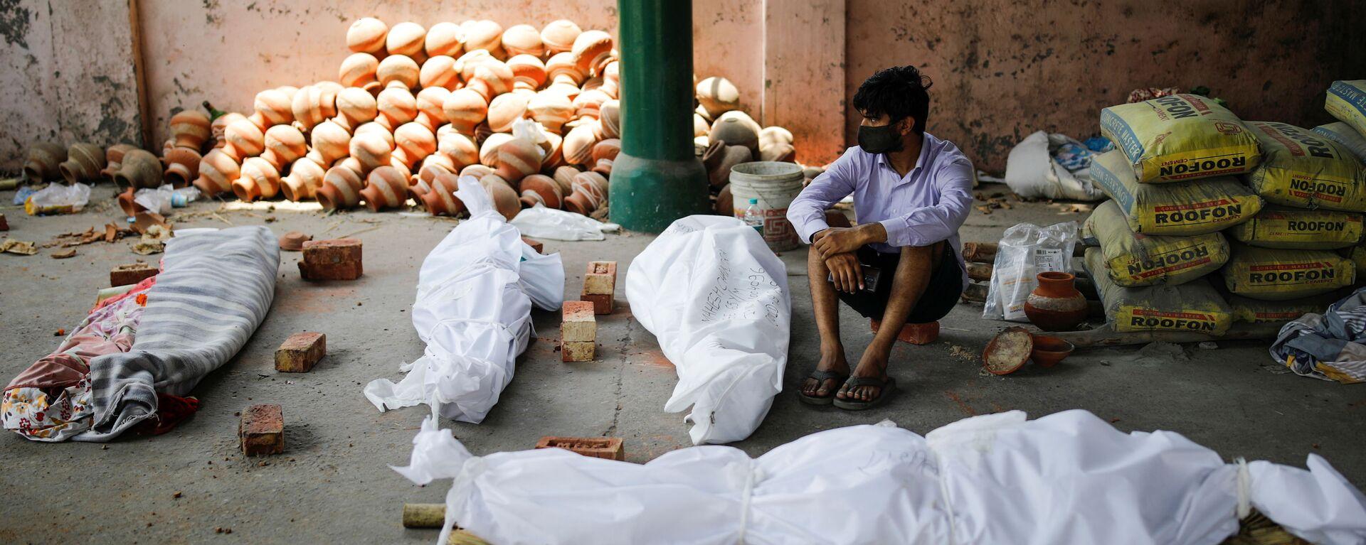 Мужчина сидит рядом с телами умерших от коронавируса перед массовой кремацией в крематории Нью-Дели, Индия - Sputnik Italia, 1920, 29.04.2021