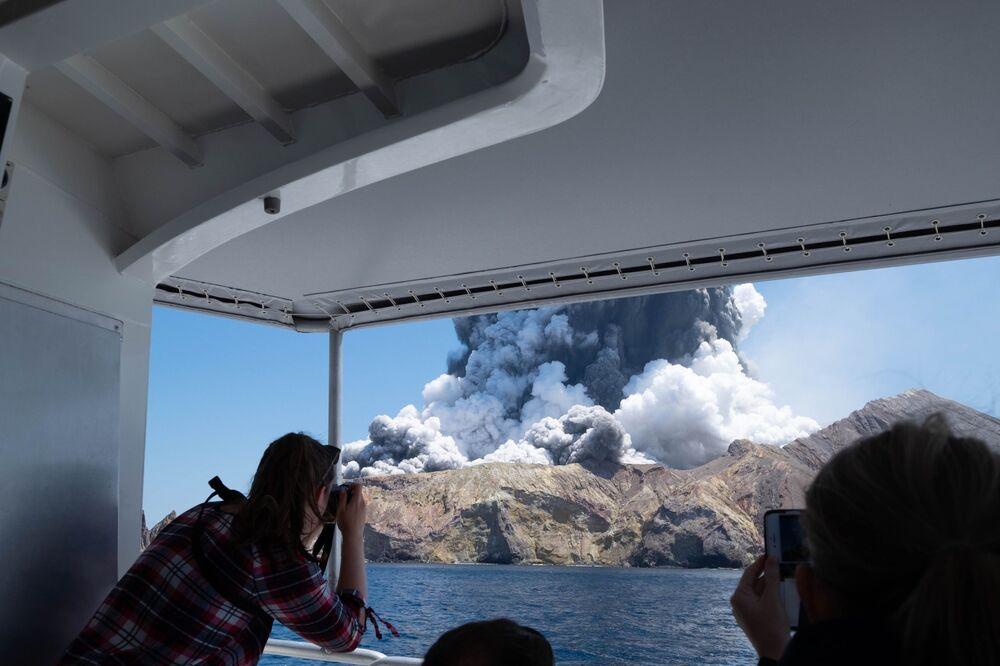Turisti fanno le foto dell'eruzione del vulcano sull'Isola Bianca in Nuova Zelanda