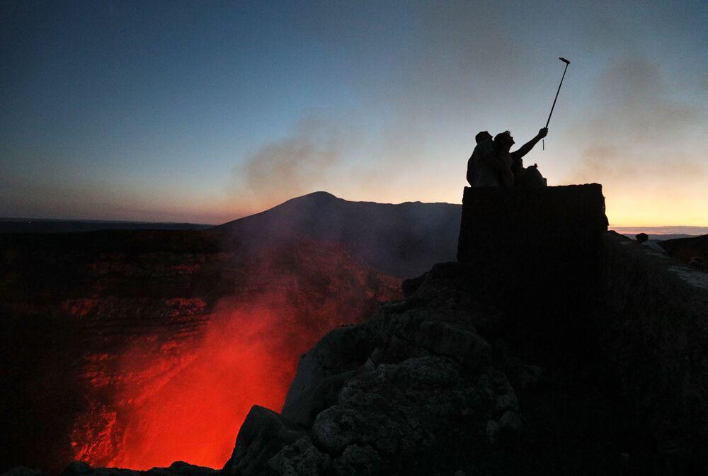 Turisti fanno le foto vicino al cratere del vulcano Masaya nel Parco Nazionale del Nicaragua