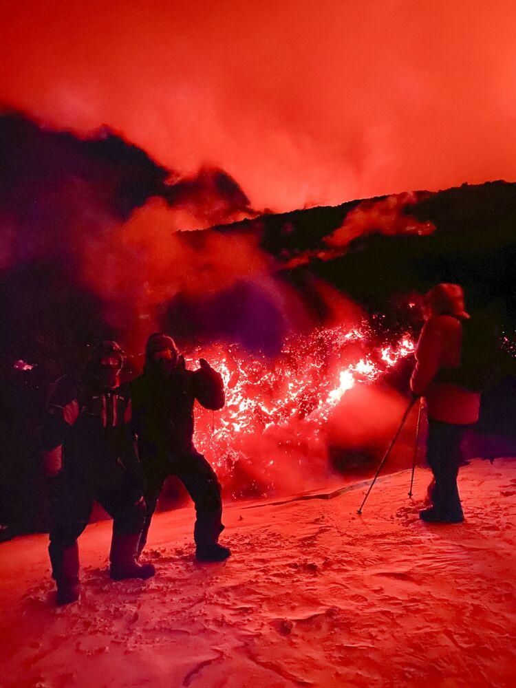 Turisti fanno le foto sullo sfondo del vulcano Klyuchevskaya Sopka nella penisola della Kamchatka (in Russia)