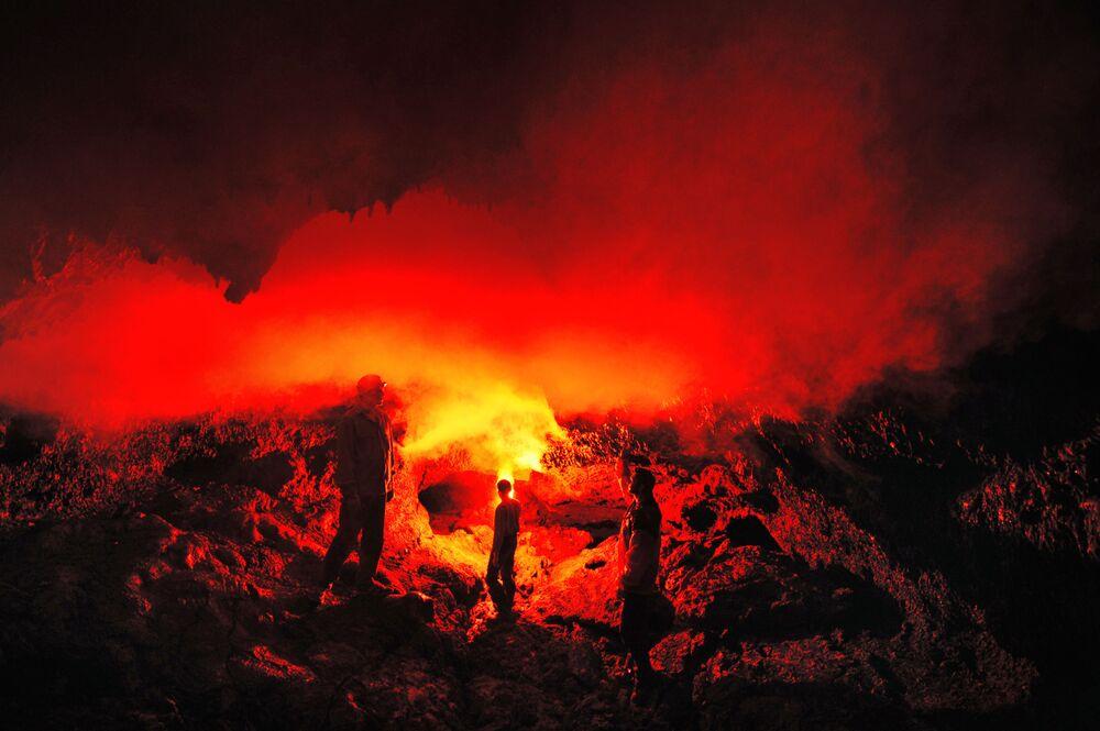 Turisti nella grotta di lava Zvezda nell'area delle aperture del vulcano Tolbachik nella penisola della Kamchatka (Russia)